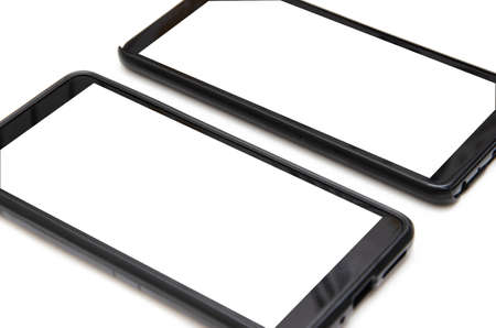Two smartphones of black color with a white screen lie on a white background nearby, deviated from each other, top view and bottom from an angle in macro