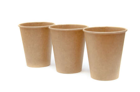 Brown paper cup for coffee, tea, a drink from environmental materials on a white background. Three glasses stand one after another diagonally. Glasses go far into perspective