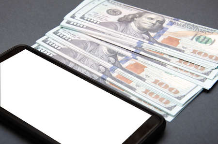 Dollars and smartphone. Denominations of 100 dollars are on a black background on them, next to them is a smartphone with a white screen. Top view and angle. Macro smartphone and dollars