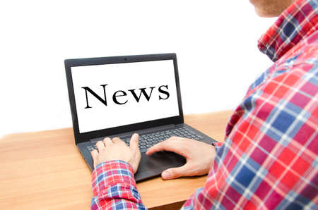 A man with a laptop. A guy in a checkered red shirt sits at a table in front of him a notebook with a white screen and the inscription news. A man reads news on a laptop