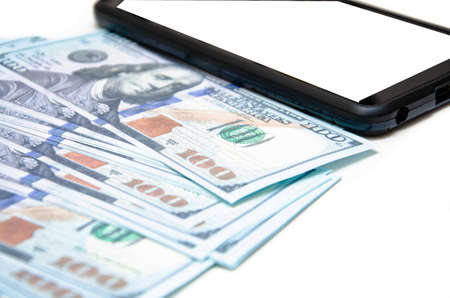 Dollars and smartphone. Banknotes in denominations of 100 dollars lie on a white background on them, next to them lies a smartphone with a white screen. Top view and angle. Macro smartphone and dollars