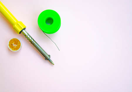 Soldering iron, tin, rosin on a yellow background. Macro Repair of electrical equipment, radio engineering. Solder wires, contacts. Copy space