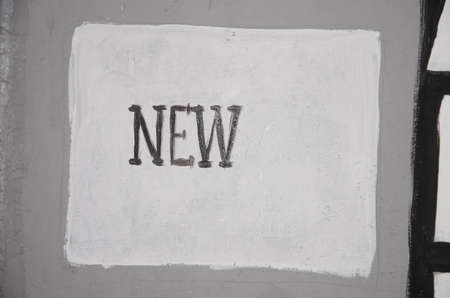 The inscription ,, New ,, on a white square on the wall. Inscription paint on the wall