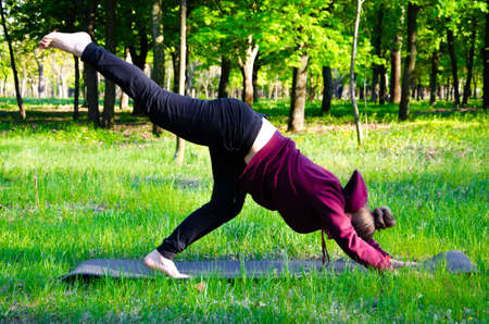The girl on the street in the karemat practices sports and yoga. The girl goes in for sports in the forest 스톡 콘텐츠