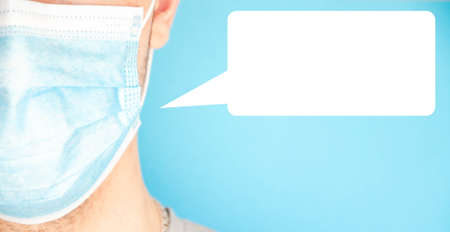 A guy in a medical mask on a blue background with a dialog box with place for text. Copy space