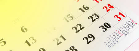 Macro calendar from different angles on a yellow and pink background. Black and red numbers on the calendar. Copy space