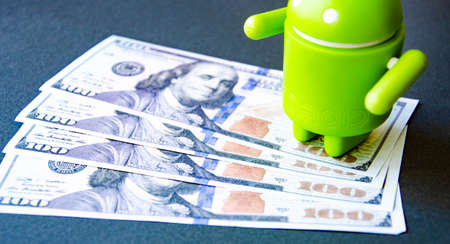March 2020. Kramatorsk, Ukraine. Green android figurine on different backgrounds, along with dollars. Banknotes dollars in the background. Android and dollars