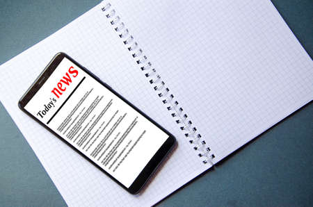 A smartphone on the screen the inscription financial news lies next to a notebook and pen