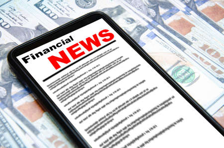The smartphone on the screen the inscription financial news lies on dollars. 100 dollars banknotes and smartphone with financial news. Banque d'images