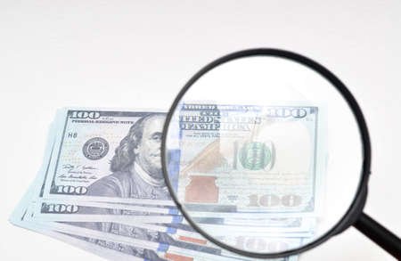 Magnifying glass and dollars on a white background. 100 dollars banknote view through a magnifying glass Фото со стока