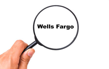 Wells Fargo on a white background view through a magnifying glass. Male hand holds a magnifying glass.