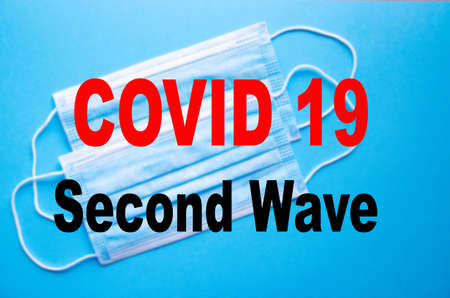 Covid 19 second wave. Covid 19. Blue medical mask on blue, yellow, black background and the inscription Covid 19 second wave