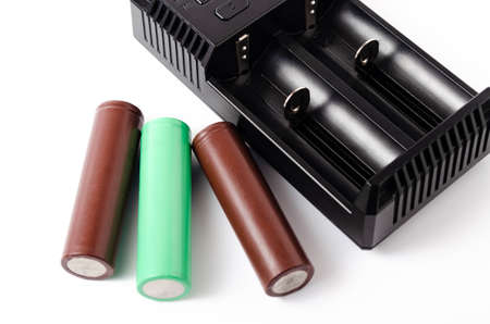 A black charger for two 18650 batteries. A green and brown 18650 battery on a white background next to the discharge, on charging. Male hand puts the battery on charge