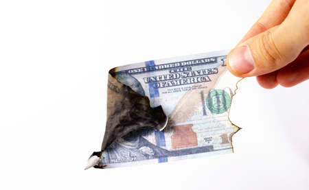 American dollars in a man's hand on a white background first-person view. Burnt dollars. Dollars are burning, Ashes, fire