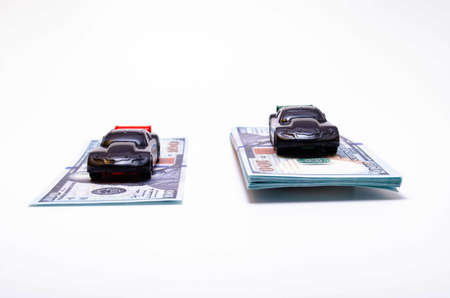 Two sports cars in black on two piles, piles of dollar bills podium. One pile, a pile more, another less. The difference in the price of the car. Buy, sell, rise and fall of prices in the market