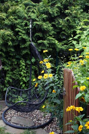 A metal swinger in a green corner of the garden