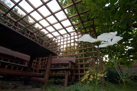 Wooden garden furniture standing in the gazebo with airy walls