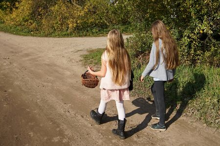 Long-haired girls walking with a basket by a dirt road by a field in autumn in the countryside