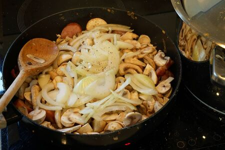 frying meat, mushrooms and onions - ingredients of a traditional Polish dish - bigos Stock Photo