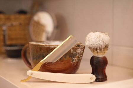 razor, shaving brush and foam dish in the bathroom