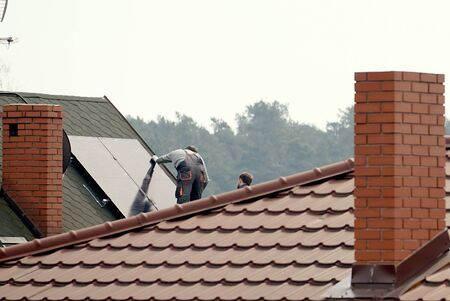 workers install solar panels on the house roof