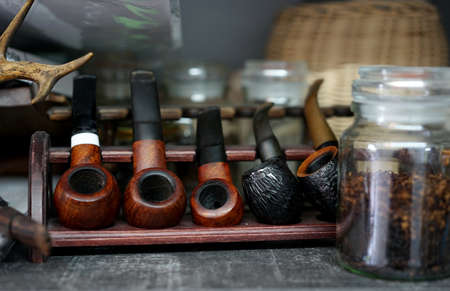 a collection of old briar pipes for smoking on a stand