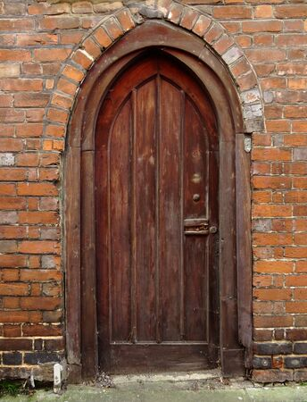 wood panel: A Victorian Arched Red Wood Paneled Door Surrounded by a Brick and Concrete Curved Archway