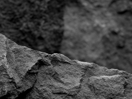 A Rough Textured Rock with Foreground Focus with a Stone Blurred Black and White Background Фото со стока