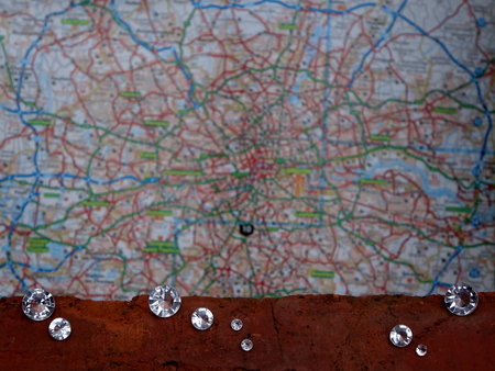 Scattered Diamonds Showing the Facet Cut of the Gem Stone on an Old House Brick with a Blurred London Map Background. Stock Photo