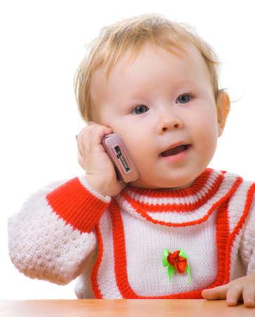 kid talking on a cellular phone. Isolation on white. Foto de archivo