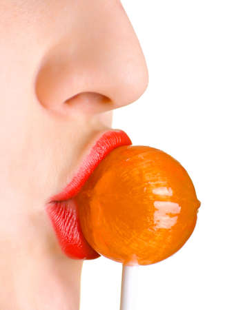 A women with the brightly painted lips sucks a lollipop candy. Shallow DOF. Stock Photo