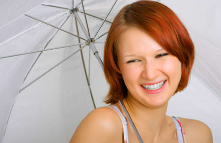 likable: a likable girl is with a smile under an umbrella