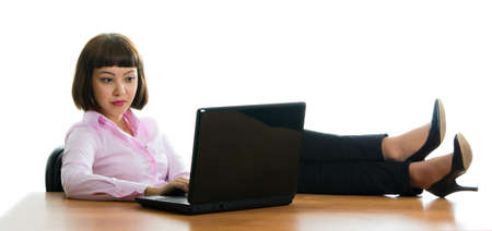 girl, working in an office sits in the workplace, laying legs on a table photo