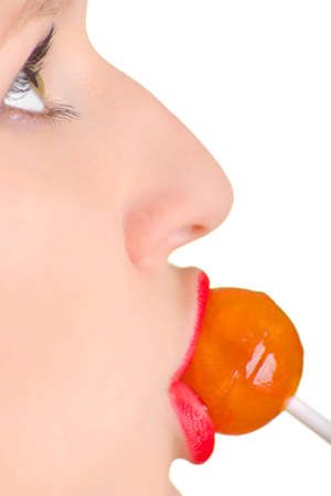 A women with the brightly painted lips sucks a lollipop candy. Shallow DOF. photo
