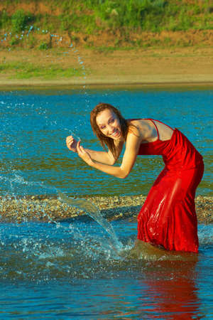 The girl in red dress fun, splashing in the river on a hot day Stock Photo