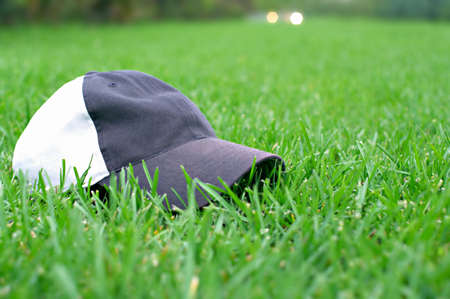 gray baseball cap on a green lawn as a symbol of active lifestyle