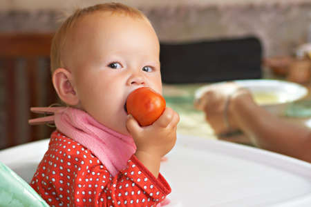 independent kid eats a tomato, sitting at the table