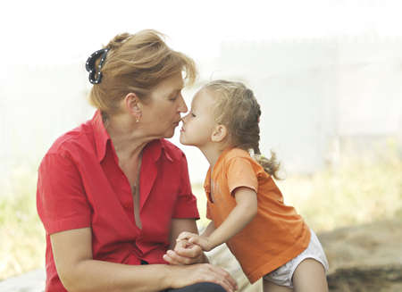 Grandma kisses granddaughter. They sit under the open sky on a summer day.