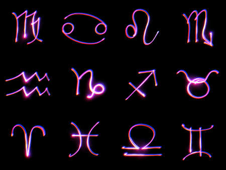 Signs of the zodiac on a black background. The technology of drawing with light - freezelight. photo