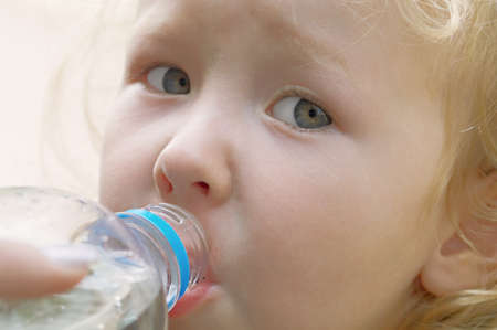 The little girl is drinking clean water close up Stock Photo