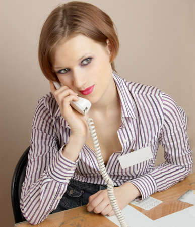 Beautiful young girl with a telephone handset. Office worker. Stock Photo