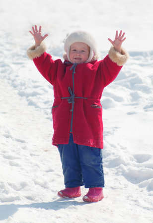 specificity: Warmly dressed child raises his hands up and was glad the weather is good