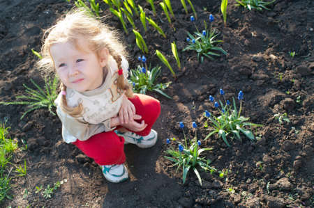 carefree little girl sitting on a bed of flowers