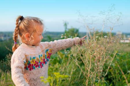 A little girl walking in the open-air. Her illuminates the evening sun.