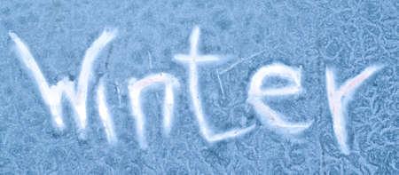 "Inscription ""winter� on the frozen glass. Winter background."