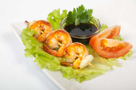 Japanese yakitori with shrimp on a white plate