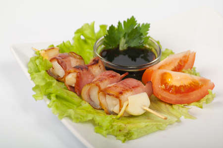 Japanese yakitori with the heart and bacon on a white plate