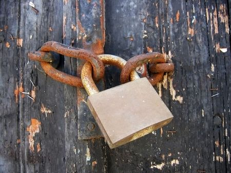 Wooden door with a rusty old padlock  Stock Photo - 3561928