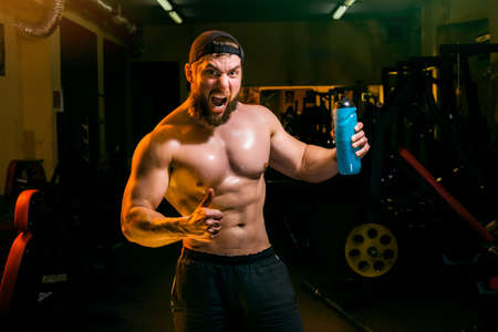 body posture: man in the gym drinking from the shaker Stock Photo