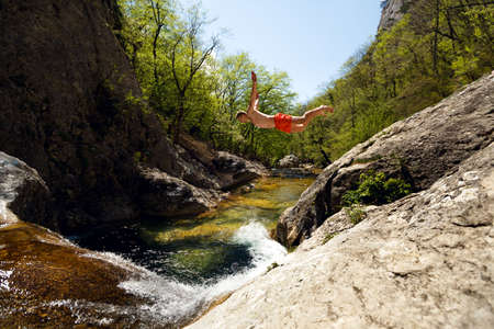 Young Man Jumping From Cliff Into Water of Mountain River Stock Photo